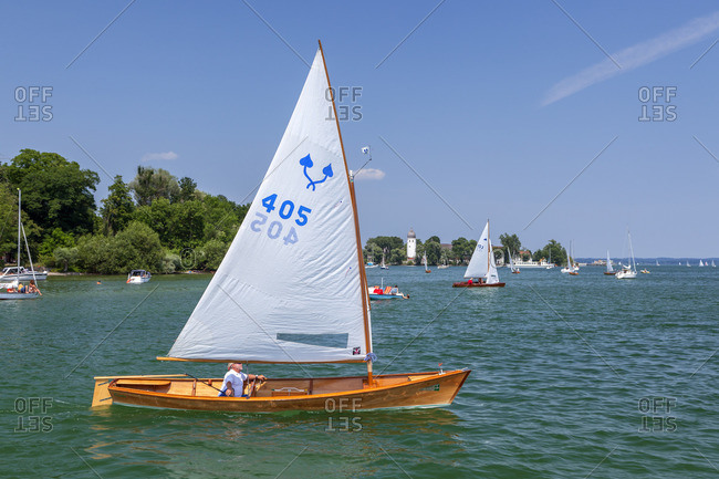 July 11, 2015: Sailor Chiemseeplatte on Lake Chiemsee behind it Fraueninsel, Frauenchiemsee, Chiemgau, Upper Bavaria, Bavaria, Southern Germany, Germany, Europe
