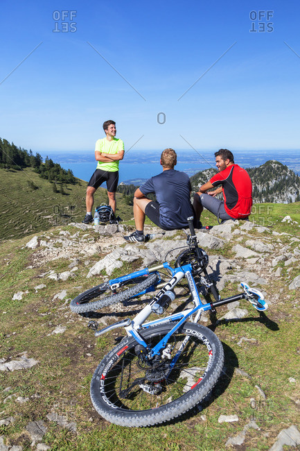 August 26, 2015: Mountain bikers at the Steinlingalm at the Kampenwand behind it the Chiemsee, Aschau, Chiemgau Alps, Chiemgau, Upper Bavaria, Bavaria, southern Germany, Germany, Europe