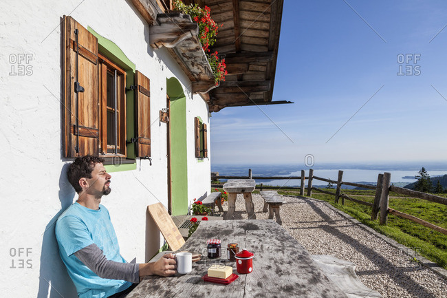 Breakfast on the terrace of the Piesenhauser alp with views of the Chiemsee, Chiemgau Alps, Marquartstein, Chiemgau, Upper Bavaria, Southern Germany, Germany, Europe