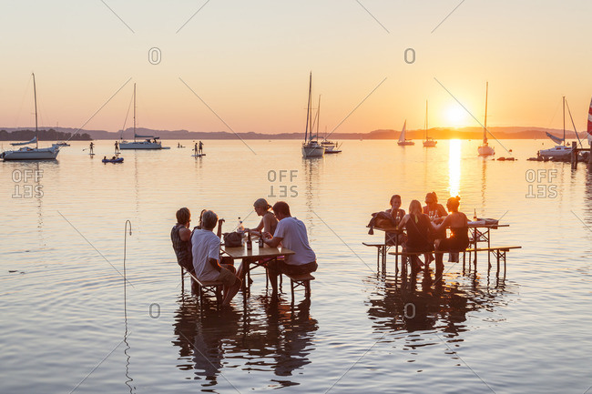 August 29, 2015: Tables in the water, sundowner bar in Ubersee am Chiemsee, Chiemgau, Upper Bavaria, Bavaria, southern Germany, Germany, Europe