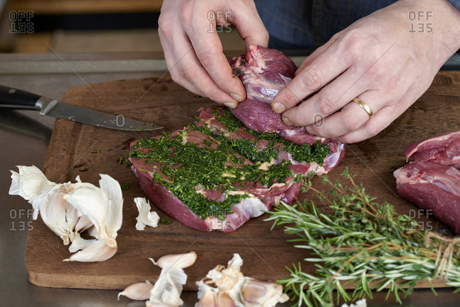 Photo series, step-by-step preparation of a leg of lamb filled with herbs and Provençal vegetables by using a food processor , rolling the leg of lamb