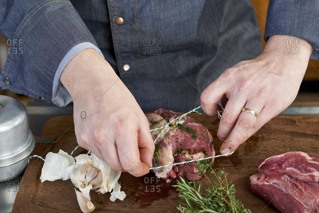 Photo series, step-by-step preparation of a leg of lamb filled with herbs and Provençal vegetables by using a food processor , trussing the leg of lamb
