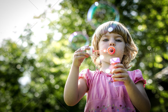 Blonde girl in pink dress blowing soap bubbles
