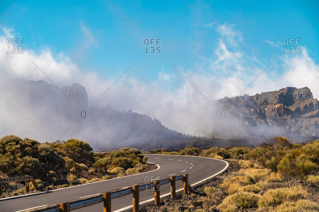 Road in Teide national park on high altitude with clouds