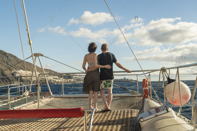 Couple hugging on a boat in the atlantic ocean by Tenerife