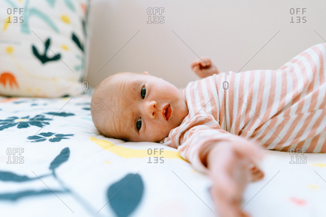 Closeup portrait of a baby girl laying on a colorful comforter