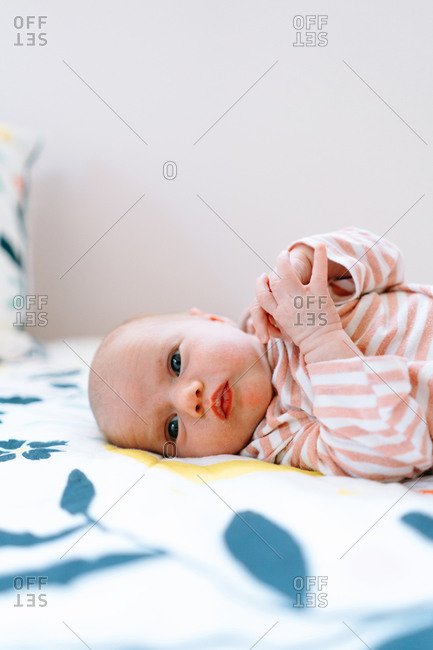Closeup portrait of a newborn baby girl laying on a colorful blanket