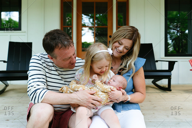 A new family sitting together on a modern farmhouse porch
