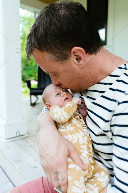 A new dad kissing his newborn baby girl on the forehead