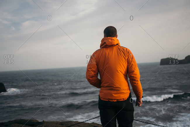 Youngman standing at windy beach of Drollery, Iceland