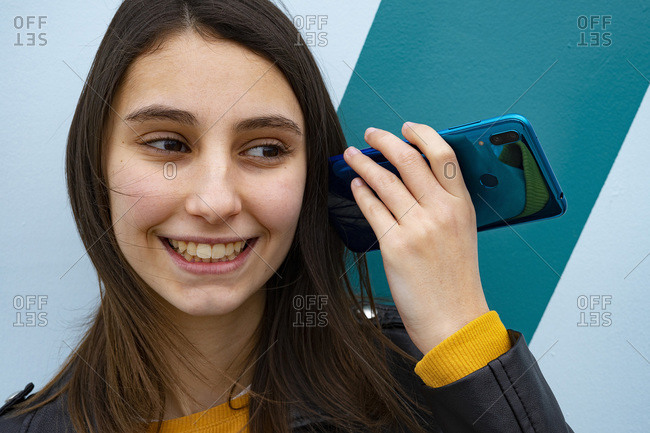Woman listening an audio with her mobile phone.