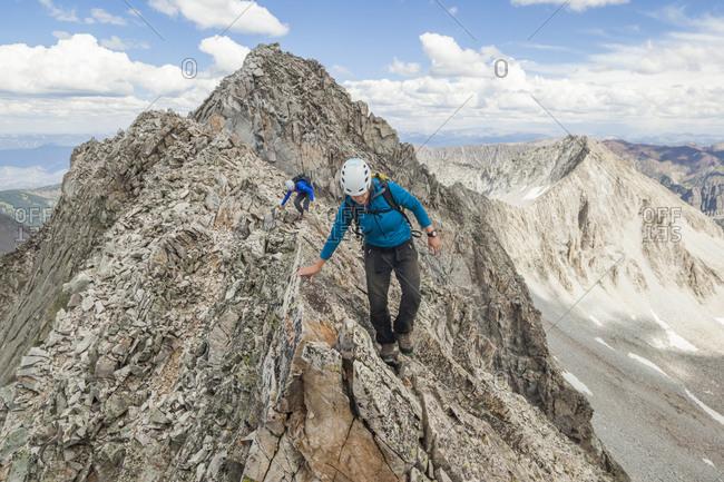 Women climb narrow ridge on Capitol Peak, Elk Mountains, Colorado