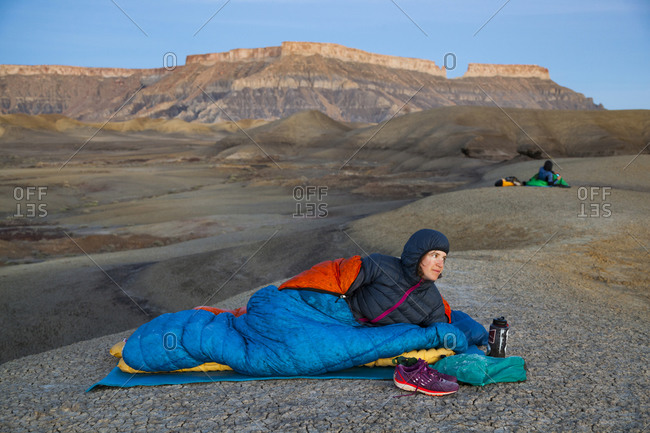 People watch sunrise from camp in Factory Butte badlands, Utah