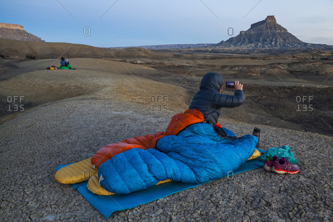 People photograph sunrise from camp in Factory Butte badlands, Utah