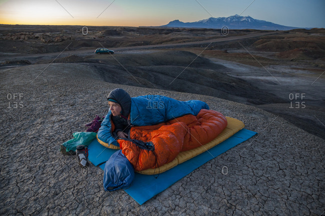 Woman watches sunrise from camp in Factory Butte badlands, Utah