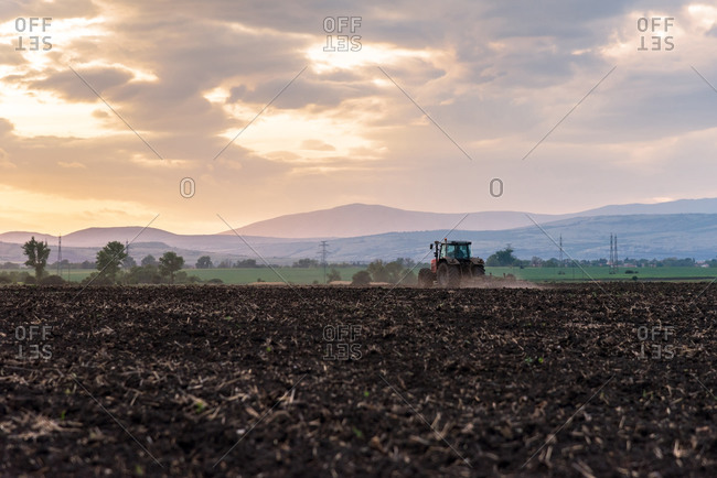 Tractor plowing fields at sunset.