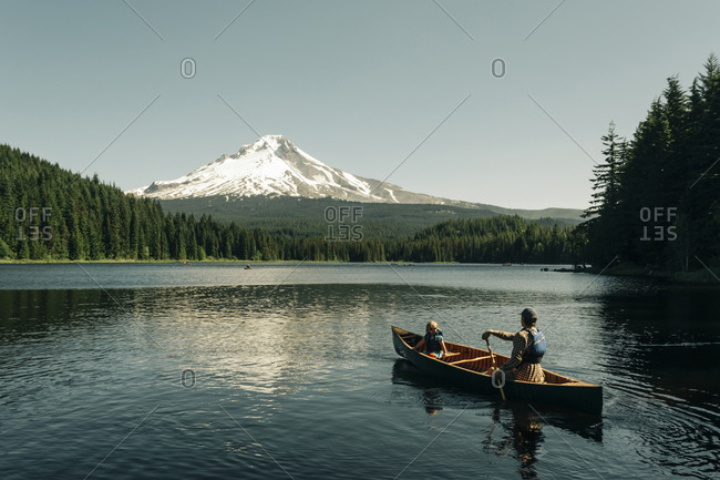 A father canoes with his daughter on Trillium Lake near Mt. Hood, OR.