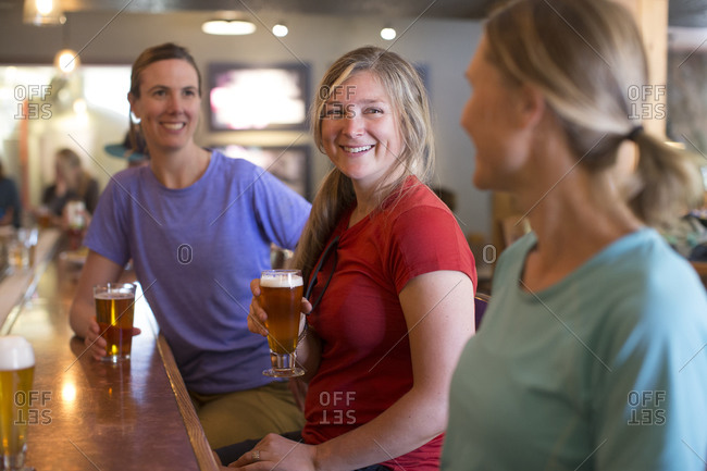 Three female friends enjoy a beer at a brewery in Government Camp, OR.