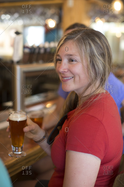 A young woman enjoys a beer with her friends at a bar in Oregon.