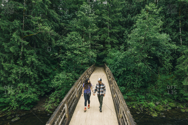 A young couple enjoys a hike on a boardwalk in the Pacific Northwest.