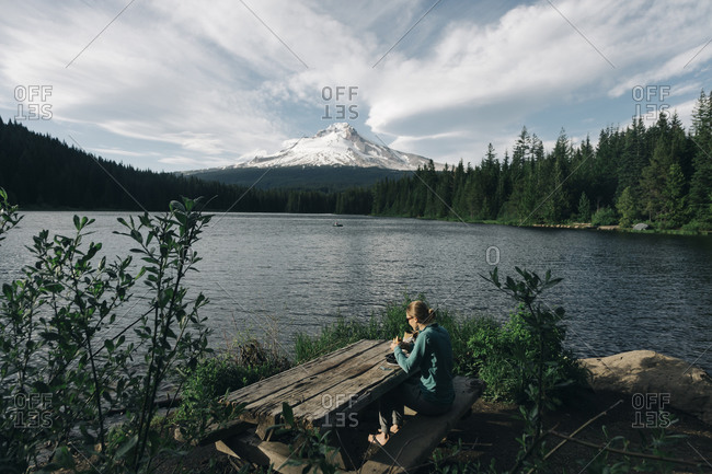 A young woman eats lunch at picnic table next to a lake near Mt. Hood.