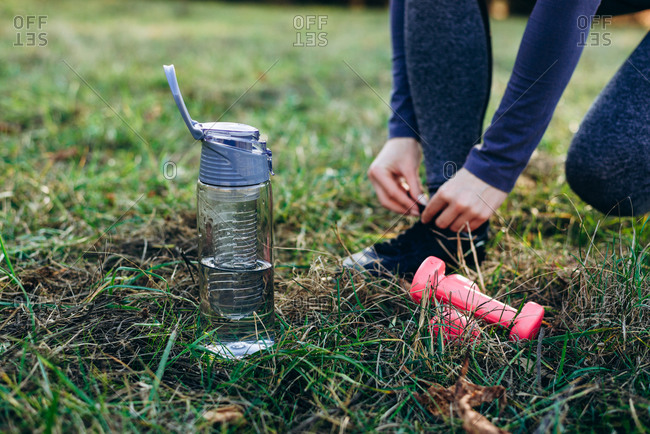 Fitness in the park, girl tying the shoe, foot bottle and dumbbells, close up.
