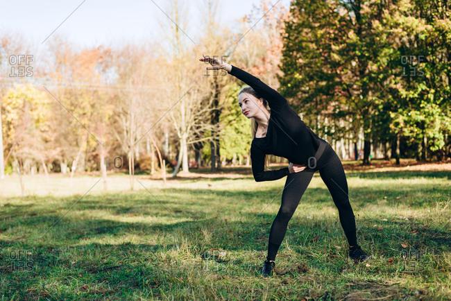Girl in black sportswear performs exercise tilt left outdoors, autumn day.