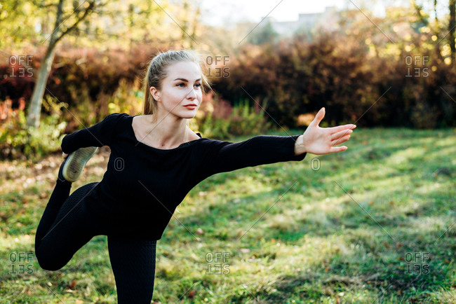 Young girl in black sportswear in a balancing pose outdoors.
