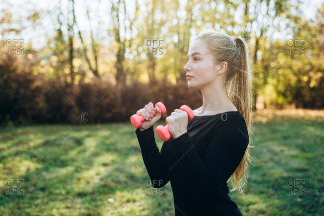 Profile of slim girl with dumbbells outdoors. Fitness in park.