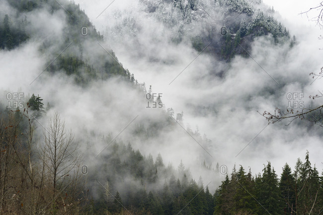 Fog and clouds rolling through snow covered mountains
