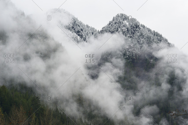 Snow Covered Mountain Peaks With Fog