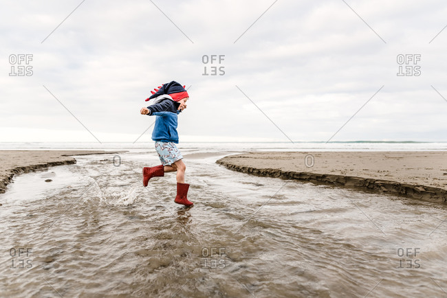 Young child wearing knit dinosaur hat jumping at beach