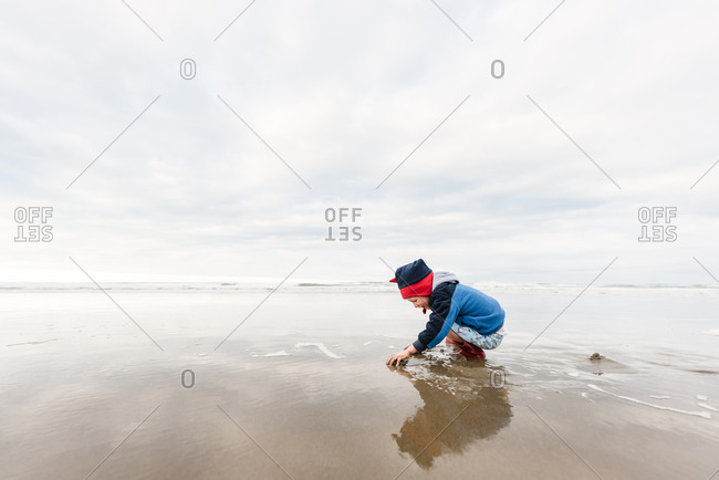 Preschooler playing at beach in winter