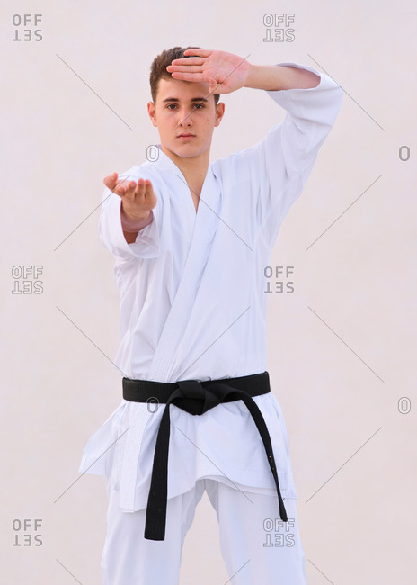teenager boy karate expert practicing fighting positions with hi