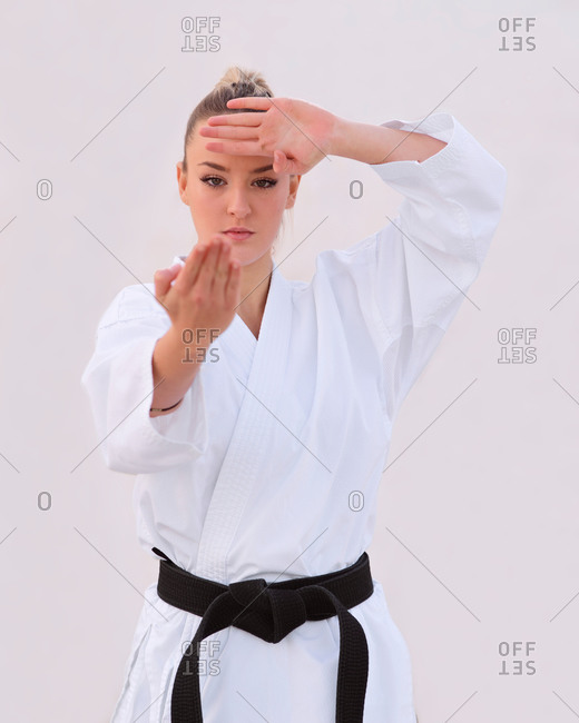Young female karate expert practicing fighting positions with he