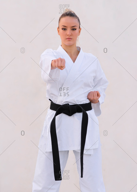 Young female karate expert practicing fighting positions with her kimono