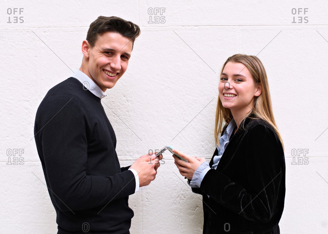 Young guy and girl with modern and urban look chat with their mo.