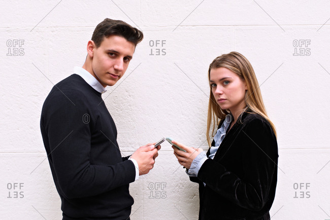Young boy and girl of modern and urban look chat with their mobile