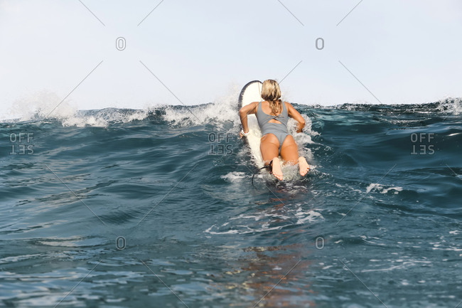 Young woman lying on surfboard in the ocean
