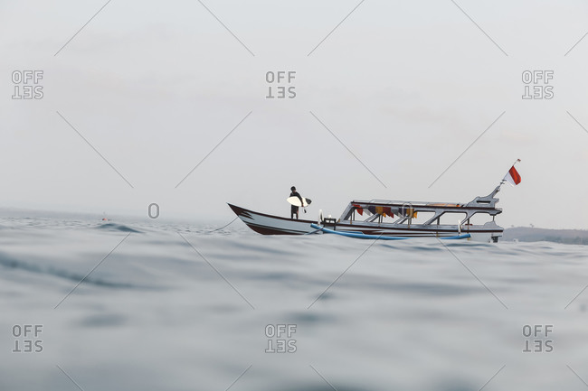 Surfer on the boat in an ocean