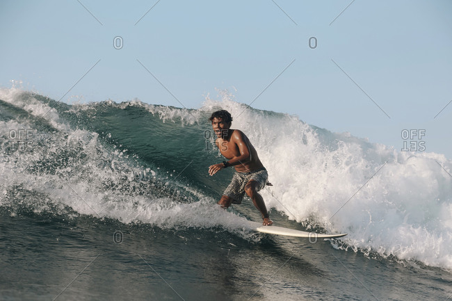 Surfer on a wave at sunset time