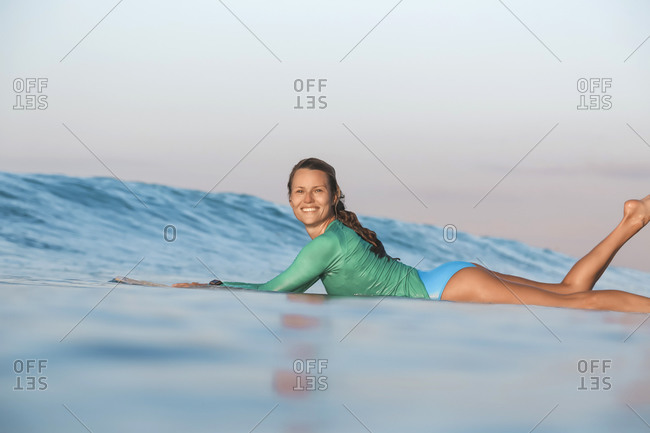 Smiling young woman lying on surfboard