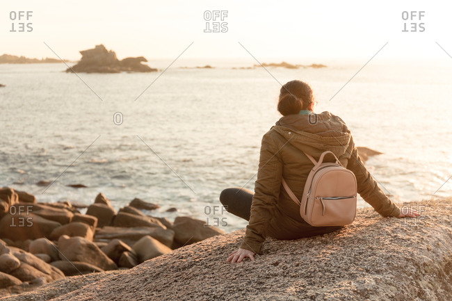 Woman sits relaxed at sunset, on the coast. Ribeira, Galicia, Spain