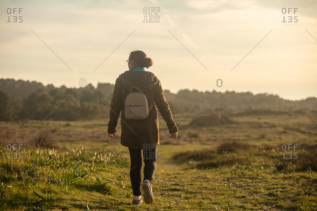 Woman with a small backpack walking through a natural grassland