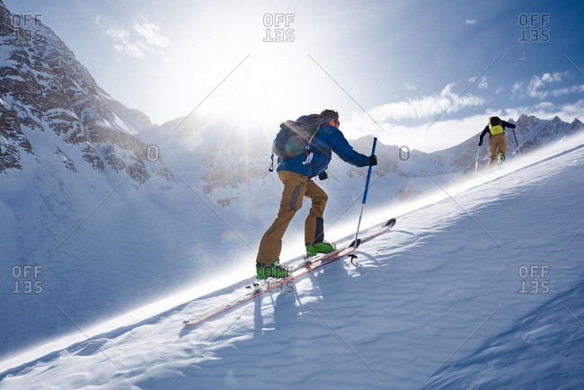 Man ski touring up hill in the wind and backlit by the sun