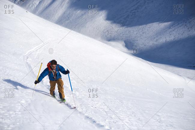 Man in blue jacket ski touring uphill