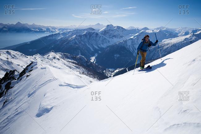 Man in blue jacket ski touring up ridge