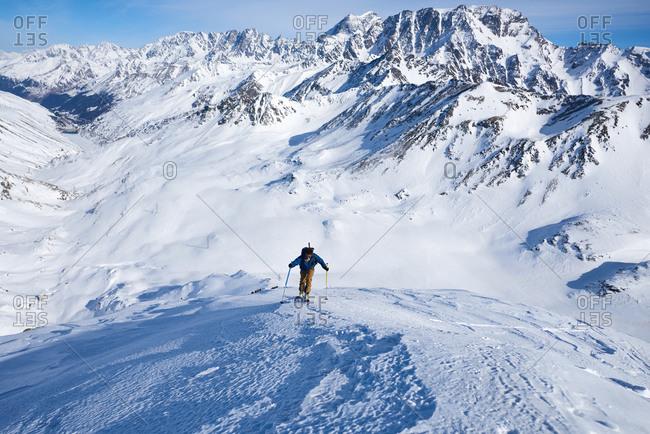 Man ski touring up slow with mountain behind him