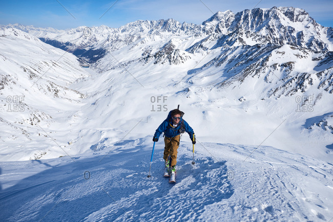 Man ski touring up slope with mountains behind him