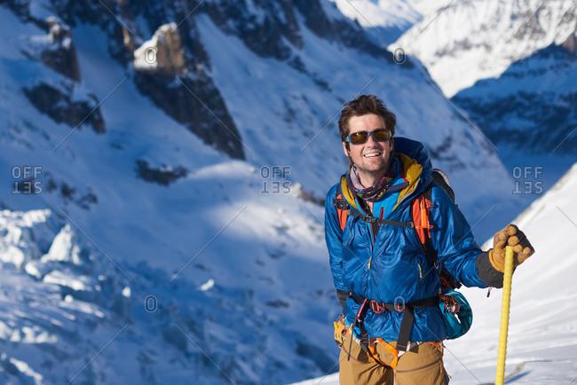 Smiling man in blue jacket stood still on a glacier